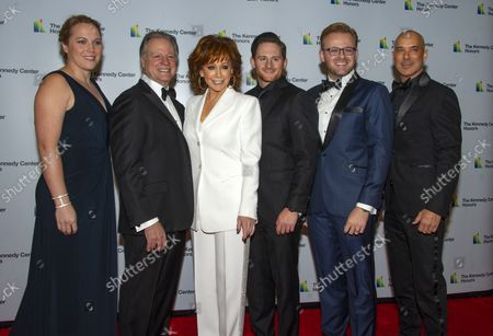 Reba McEntire arrives with her family for the formal Artist's Dinner honoring the recipients of the 41st Annual Kennedy Center Honors hosted by United States Deputy Secretary of State John J. Sullivan at the US Department of State in Washington, D.C. on Saturday, December 1, 2018. Pictured from left to right: Marne McLyman, Skeeter Lasuzzo, Reba McEntire, Shelby Blackstock, Justin McIntosh, and Brett Freedman.  The 2018 honorees are: singer and actress Cher; composer and pianist Philip Glass; Country music entertainer Reba McEntire; and jazz saxophonist and composer Wayne Shorter. This year, the co-creators of Hamilton,  writer and actor Lin-Manuel Miranda, director Thomas Kail, choreographer Andy Blankenbuehler, and music director Alex Lacamoire will receive a unique Kennedy Center Honors as trailblazing creators of a transformative work that defies category.