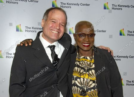 Stock Picture of Singer Angelique Kidjo, right, and Kevin Morris arrive for the formal Artist's Dinner honoring the recipients of the 41st Annual Kennedy Center Honors hosted by United States Deputy Secretary of State John J. Sullivan at the US Department of State in Washington, D.C. on Saturday, December 1, 2018. The 2018 honorees are: singer and actress Cher; composer and pianist Philip Glass; Country music entertainer Reba McEntire; and jazz saxophonist and composer Wayne Shorter. This year, the co-creators of Hamilton, writer and actor Lin-Manuel Miranda, director Thomas Kail, choreographer Andy Blankenbuehler, and music director Alex Lacamoire will receive a unique Kennedy Center Honors as trailblazing creators of a transformative work that defies category.