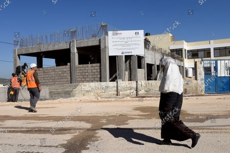 Stock Photo of A Palestinian woman walks past construction workers renovating and building an extension to the girl's school in Al-Jabba, near Bethlehem, West Bank, which is funded by USAid, United States Agency for International Development, January 23, 2019. The $1.4 million dollar project will be terminated at the end of January because U.S. President Donald Trump's administration will stop funding Palestinian projects and also because Palestinian Prime Minister Rami Hamdallah has stated that the Palestinian Authority will cease accepting funding from America. The school will be unusable for the 250 girl students who attend the school.