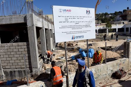 Stock Image of Palestinian construction workers renovate and build an extension to the girl's school in Al-Jabba, near Bethlehem, West Bank, which is funded by USAid, United States Agency for International Development, January 23, 2019. The $1.4 million dollar project will be terminated at the end of January because U.S. President Donald Trump's administration will stop funding Palestinian projects and also because Palestinian Prime Minister Rami Hamdallah has stated that the Palestinian Authority will cease accepting funding from America. The school will be unusable for the 250 girl students who attend the school.