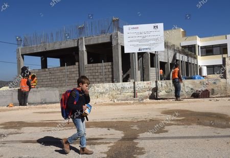 Stock Picture of A Palestinian boy eats while walking by construction workers renovating and building an extension to the girl's school in Al-Jabba, near Bethlehem, West Bank, which is funded by USAid, United States Agency for International Development, January 23, 2019. The $1.4 million dollar project will be terminated at the end of January because U.S. President Donald Trump's administration will stop funding Palestinian projects and also because Palestinian Prime Minister Rami Hamdallah has stated that the Palestinian Authority will cease accepting funding from America. The school will be unusable for the 250 girl students who attend the school.