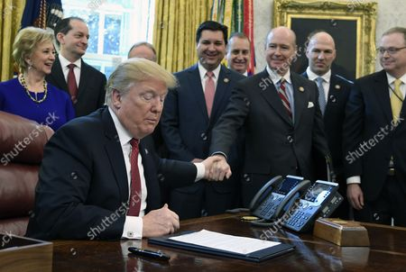 """President Donald Trump reaches out to Rep. Robert Aderholt (Alabama) as he makes remarks to workers from American manufacturing industries, during a meeting that included Rep. David Rouzer (C) of North Carolina, SBA Administrator Linda McMahon (L) and Secretary of Labor Alex Acosta (2nd, L)at the White House, Washington, DC, January 31, 2019.  Trump signed an Executive Order encouraging recipients of federal financial assistance to """"Buy American""""."""
