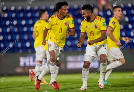 Colombia's Juan Cuadrad, left, celebrates with teammate Miguel Borja after scoring from the penalty spot his side's opening goal against Paraguay during a qualifying soccer match for the FIFA World Cup Qatar 2022 in Asuncion, Paraguay