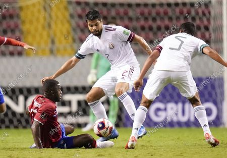 Costa Rica's Joel Campbell, ground, and Mexico's Alejandro Araujo battle for the ball during a qualifying soccer match for the FIFA World Cup Qatar 2022, in San Jose, Costa Rica
