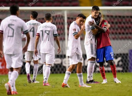 Stock Photo of Mexico's Cesar Montes, second right, embraces Costa Rica's Joel Campbell at the end of a qualifying soccer match for the FIFA World Cup Qatar 2022, in San Jose, Costa Rica, . Mexico won the game 1-0