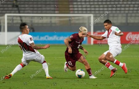 Venezuela's Yeferson Soteldo, center, is challenged by Peru's Christian Cueva, left, and Peru's Edison Flores during a qualifying soccer match for the FIFA World Cup Qatar 2022 at National stadium in Lima, Peru
