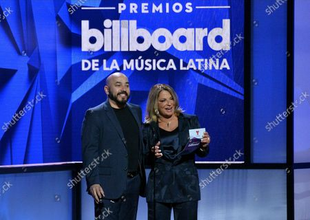 Stock Photo of Dra Polo and Lupillo Rivera (R) present an award onstage during the 26th annual Billboard Latin Music Awards at the Mandalay Bay Events Center in Las Vegas, Nevada on April 25, 2019.