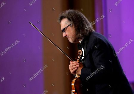 Stock Picture of Greek violinist Leonidas Kavakos reacts after performing Tchaikovsky's Violin Concerto in D major Op.35, accompanied by The Munich Philharmonic orchestra under the baton of Russian conductor Valery Gergiev, on the stage of Grand Palace Hall during Enescu Festival 2021, in Bucharest, Romania, 06 September 2021. The festival, held every two years since 1958, is the biggest classical music festival held in Romania and is named after Romanian composer and violinist George Enescu. The 2021 edition runs from 28 August to 26 September 2021 with the participation of 32 orchestras from 14 countries, totaling 3,500 foreign and Romanian artists. Special measures are being taken to reduce health risks for spectators and artists.