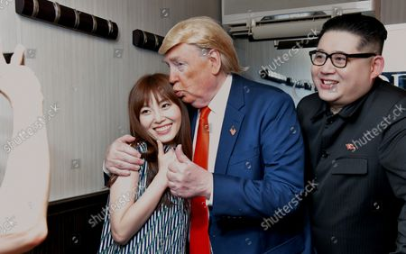 (R-L) Howard X, impersonating North Korean leader Kim Jong Un, Dennis Alan, impersonator of U.S. President Donald Trump and guest pose for photographers at Jazz Bar in Osaka, Japan on Thursday, June 27, 2019.