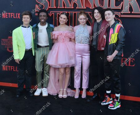 """Cast members Gaten Matarazzo, Caleb McLaughlin, Millie Bobby Brown, Sadie Sink, Finn Wolfhard, and Noah Schnapp (L-R) Gaten Matarazzo, Caleb McLaughlin, Millie Bobby Brown, Sadie Sink, Finn Wolfhard, and Noah Schnapp (L-R) attend the premiere of the sci-fi TV horror series """"Stranger Things 3"""" at Santa Monica High School in Santa Monica, California on Friday, June 28th, 2019. Storyline: In a small town where everyone knows everyone, a peculiar incident starts a chain of events that leads to the disappearance of a child, which begins to tear at the fabric of an otherwise peaceful community. Dark government agencies and seemingly malevolent supernatural forces converge on the town, while a few locals begin to understand that there's more going on than meets the eye."""
