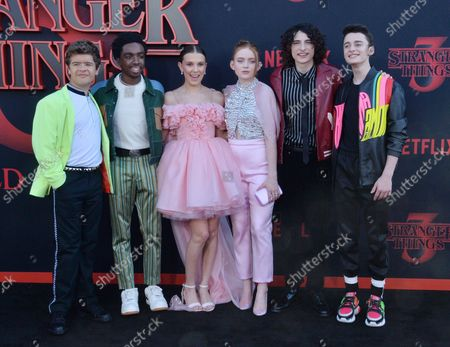 """Cast members Gaten Matarazzo, Caleb McLaughlin, Millie Bobby Brown, Sadie Sink, Finn Wolfhard, and Noah Schnapp.(L-R) Gaten Matarazzo, Caleb McLaughlin, Millie Bobby Brown, Sadie Sink, Finn Wolfhard, and Noah Schnapp (L-R) attend the premiere of the sci-fi TV horror series """"Stranger Things 3"""" at Santa Monica High School in Santa Monica, California on Friday, June 28th, 2019. Storyline: In a small town where everyone knows everyone, a peculiar incident starts a chain of events that leads to the disappearance of a child, which begins to tear at the fabric of an otherwise peaceful community. Dark government agencies and seemingly malevolent supernatural forces converge on the town, while a few locals begin to understand that there's more going on than meets the eye."""