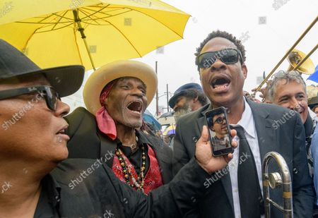 Stock Photo of Dumpstaphunk musician Ivan Neville uses a FaceTime app to sing with his son Ian Neville and his uncle Cyril Neville, second left, and trombonist Corey Henry as they take part in a memorial second line in the rain for Art 'Poppa Funk' Neville, a co-founder of the Grammy-winning Neville Brothers and The Meters, in New Orleans, Tuesday, July 30, 2019. Arthur Lanon Neville (December 17, 1937 Ð July 22, 2019) was known for New Orleans standards 'Hey Pocky A-Way,' 'Fire on the Bayou,' and 'Mardi Gras Mambo.' He was a pioneer of funk and New Orleans music.