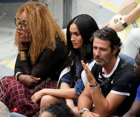 Meghan, Duchess of Sussex, sits with Oracene Price (L), Serena Williams' mother, and her coach Patrick Mouratoglou (R) as they watch Serena Williams, of the United States, lose to Bianca Andreescu, of Canada, in the Woman's Championship at the 2019 US Open Tennis Championships at the USTA Billie Jean King National Tennis Center on Saturday. September 7, 2019 in New York City.