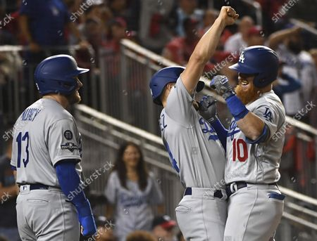 Los Angeles Dodgers third baseman Justin Turner (10) celebrates with teammates Like Hernandez (C) and Max Muncy after hitting a solo home run against the Washington Nationals in the sixth inning during the National League Division Game Three at Nationals Park in Washington, D.C. on October 6, 2019. Washington and Los Angeles enter game three tied 1-1 in the five-game series.