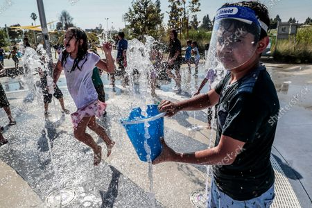 """Los Angeles, CA, Monday, Sept. 6, 2021 -Edgar Barajas fills a bucket with water as he prepares to douse his father Aurelio Bergata as others also frolic in a playground water fountain at Earvin """"Magic"""" Johnson Park. (Robert Gauthier/Los Angeles Times)"""
