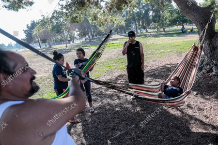 """Los Angeles, CA, Monday, Sept. 6, 2021 - Manuel Cabrera rocks his son, Moises, 7, in a hammock as the family stands by during a Labor Day celebration at Earvin """"Magic"""" Johnson Park. (Robert Gauthier/Los Angeles Times)"""