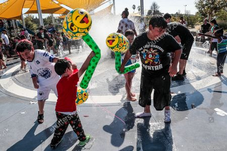 """Stock Photo of Los Angeles, CA, Monday, Sept. 6, 2021 - Children frolic in a playground water fountain at Earvin """"Magic"""" Johnson Park. (Robert Gauthier/Los Angeles Times)"""