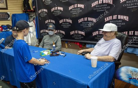 Baseball stars Reggie Jackson and Peter Rose (R) share a laugh with a young fan as they sign autographs at the Safe at Home shop in downtown near Major League Baseball's Hall of Fame in Cooperstown, New York on Tuesday, September 7, 2021.   Rose had the most hits in baseball but is not in the Hall of Fame.   Derek Jeter, Ted Simmons, Larry Walker and players' union leader Marvin Miller will be inducted into the HOF on September 8th.