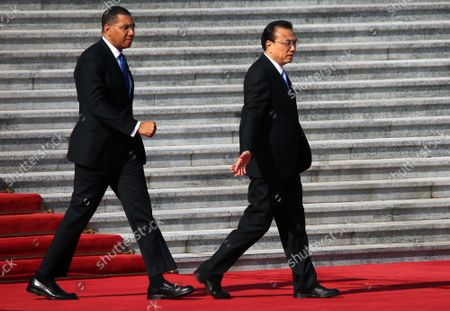 Chinese Premier Li Keqiang (R) escorts Jamaican Prime Minister Andrew Holness to a welcoming ceremony at the Great Hall of the People in Beijing on Friday, November 68, 2019.  Holness welcomed the opportunity to work with China in areas such as renewable energy, border security, agriculture, health care and STEM education to bolster Jamaica's economy.