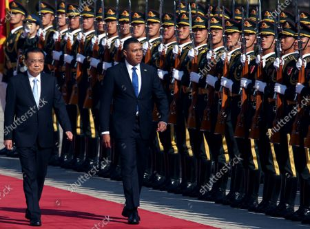 Chinese Premier Li Keqiang (L) escorts Jamaican Prime Minister Andrew Holness past a military honor guard during a welcoming ceremony at the Great Hall of the People in Beijing on Friday, November 68, 2019.  Holness welcomed the opportunity to work with China in areas such as renewable energy, border security, agriculture, health care and STEM education to bolster Jamaica's economy.
