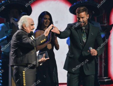 (L-R) Vicente Fernandez receives the Premio de la Presidencia award from host Ricky Martin during the 20th annual Latin Grammy Awards honoring Columbian singer Juanes at the MGM Grand Convention Center in Las Vegas, Nevada on Thursday, November 14, 2019.