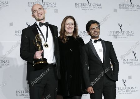 """British film maker James Watkins (L), Indian actor Nawazuddin Siddiqui and British producer Dixie Linder (R) stand in the press room with the award for """"Drama Series"""" for """"McMafia"""" at the 47th International Emmy Awards at the New York Hilton in New York City on November 25, 2019."""