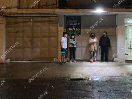 Residents take cover from the rain under an awning after an earthquake alarm sent them out of their home, in the lobby of an apartment building in the Valle del Sur neighborhood of Mexico City, . A powerful earthquake struck southern Mexico near the resort of Acapulco on Tuesday night, causing buildings to rock and sway in Mexico City nearly 200 miles away