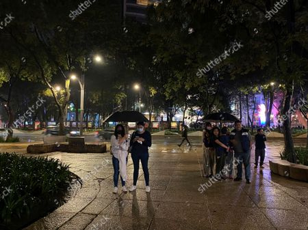 People stand under the rain after a strong earthquake on Reforma avenue in Mexico City, . The quake struck southern Mexico near the resort of Acapulco, causing buildings to rock and sway in Mexico City nearly 200 miles away