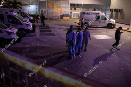 Health workers check on their mobile phones as they stand outside Veracruz General Hospital after a strong earthquake, in Veracruz, Mexico, . The quake struck southern Mexico near the resort of Acapulco, causing buildings to rock and sway in Mexico City nearly 200 miles away