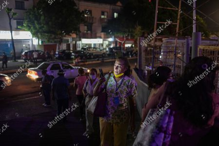 Health workers check their mobile phones as they stand outside Veracruz General Hospital after a strong earthquake, in Veracruz, Mexico, . The quake struck southern Mexico near the resort of Acapulco, causing buildings to rock and sway in Mexico City nearly 200 miles away