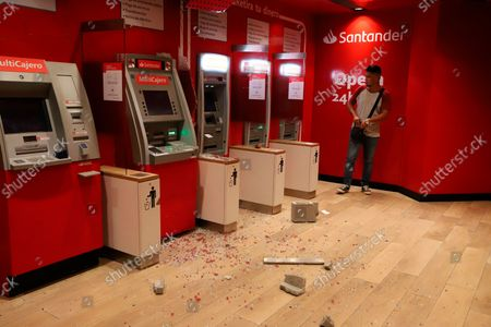 Man stands next to row of ATM's surrounded by debris after a strong earthquake, in Acapulco, Mexico, . The quake struck southern Mexico near the resort of Acapulco, causing buildings to rock and sway in Mexico City nearly 200 miles away