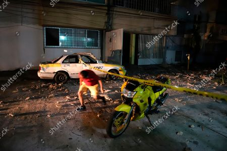 Man ducks under police tape, on a street covered with debris after a strong earthquake in Acapulco, Mexico, . The quake struck southern Mexico near the resort of Acapulco, causing buildings to rock and sway in Mexico City nearly 200 miles away