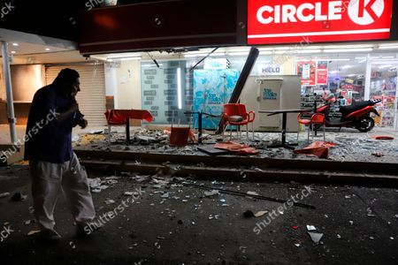 Man walks in from of a convenience store on a street covered with debris after a strong earthquake, in Acapulco, Mexico, . The quake struck southern Mexico near the resort of Acapulco, causing buildings to rock and sway in Mexico City nearly 200 miles away