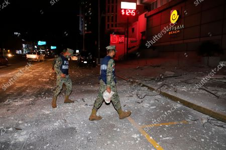 Mexican Marines walk on a street covered by debris after a strong earthquake in Acapulco, Mexico, . The quake struck southern Mexico near the resort of Acapulco, causing buildings to rock and sway in Mexico City nearly 200 miles away
