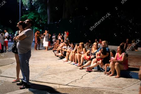 Locals sit on a sidewalk after a strong earthquake in Acapulco, Mexico, . The quake struck southern Mexico near the resort of Acapulco, causing buildings to rock and sway in Mexico City nearly 200 miles away