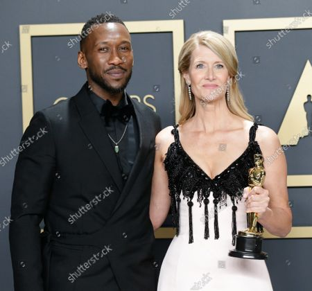 """Mahershala Ali (L), with Laura Dern, winner of the Best Actress in a Supporting Role for """"Marriage Story,"""" appears backstage with her Oscar during the 92nd annual Academy Awards at Loews Hollywood Hotel in the Hollywood section of Los Angeles on Sunday, February 9, 2020."""