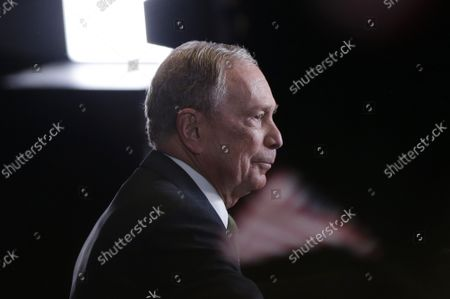 Democratic presidential candidate Mike Bloomberg waits for supporters holding American Flags to settle down before he delivers a speech announcing that he is suspending his campaign on Wednesday, March 4, 2020 in New York City. Bloomberg endorsed Joe Biden saying the former vice president had the best chance to win in November.