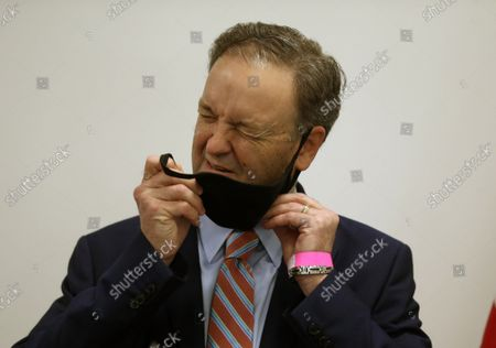 St. Louis County Executive Dr. Sam Page struggles to get his face mask off to speak to reporters, in Clayton, Missouri on Friday, May 29, 2020. Page announced that St. Louis Countyâ€s Department of Public Health has been recognized by the Centers for Medicare & Medicaid Services (CMS) for its work to protect nursing home residents during the COVID-19 pandemic.