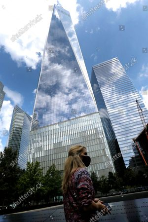 A woman visits the north memorial pool in front of One World Trade Center a few days before  the 20th anniversary of the September 11 terror attack in New York, New York, USA, 08 September 2021. On 11 September 2001, during a series of coordinated terror attacks using hijacked airplanes, two airplanes were flown into the World Trade Center's twin towers causing the collapse of both towers. A third plane targeted the Pentagon and a fourth plane heading towards Washington, DC ultimately crashed into a field. The 20th anniversary of the worst terrorist attack on US soil will be observed on 11 September 2021.