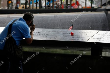 A man takes picture at the south memorial pool a few days before  the 20th anniversary of the September 11 terror attack in New York, New York, USA, 08 September 2021. On 11 September 2001, during a series of coordinated terror attacks using hijacked airplanes, two airplanes were flown into the World Trade Center's twin towers causing the collapse of both towers. A third plane targeted the Pentagon and a fourth plane heading towards Washington, DC ultimately crashed into a field. The 20th anniversary of the worst terrorist attack on US soil will be observed on 11 September 2021.