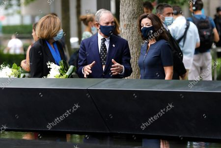 Stock Image of New York Gov. Kathy Hochul (R) and former New York City Mayor Mike Bloomberg (C) are joined by 9/11 Memorial and Museum Director Alice Greenwald (C) after  laying flowers at the edge of the south memorial pool to commemorate the 20th anniversary of the September 11 terror attack in New York, New York, USA, 08 September 2021. On 11 September 2001, during a series of coordinated terror attacks using hijacked airplanes, two airplanes were flown into the World Trade Center's twin towers causing the collapse of both towers. A third plane targeted the Pentagon and a fourth plane heading towards Washington, DC ultimately crashed into a field. The 20th anniversary of the worst terrorist attack on US soil will be observed on 11 September 2021.