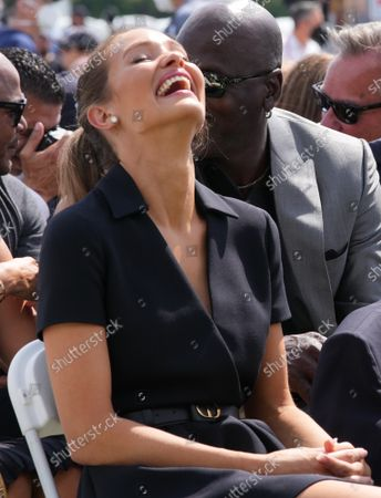 Hanna Jeter, wife of Derek Jeter,  smiles after a remark from Michael Jordan (rear) during baseball's Hall of Fame Induction Ceremony 2021 for the 2020 inductees in Cooperstown, New York on Wednesday, September 8, 2021.  Derek Jeter, Ted Simmons, Larry Walker and players' union leader Marvin Miller will be inducted into the HOF during the event.