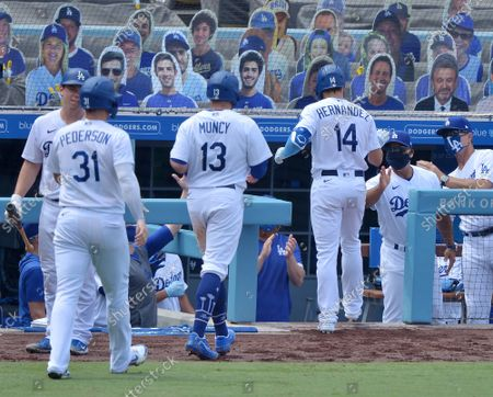 Los Angeles Dodgers' Kike Hernandez, Max Muncy and Joc Pederson return to the dugout after Hernandez hit a three-run homer off Colorado Rockies' starting pitcher Antonio Senzatela in the fourth inning at Dodger Stadium in Los Angeles on Sunday, August  23, 2020.
