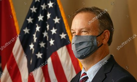 Dr. Sam Page, St. Louis County Executive, says hello to reporters through his mask before delivering new coronavirus restrictions at a daily press conference in Clayton, Missouri on Friday, November 13, 2020. Page announced restaurants and bars will have to close to indoor service but they will be able to have outdoor dining as well as drive-thru and curbside service. Gatherings will only be able to have a maximum of ten people, down from the current limit of 49 and people are being asked to form social bubbles with ten or less family members or friends and limit all interactions to that group.