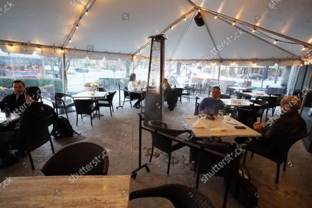 Patrons at Herbies Restaurant sit inside of a large enclosed tent with heaters in Clayton, Missouri on Tuesday, November 17, 2020. Due to the COVID-19 spreading in record numbers, St. Louis County Executive Dr. Sam Page has ordered all restaurants in St. Louis County, closed for indoor seating, however curbside pickup and outdoor seating is still permitted. All people over five years of age must wear a mask when leaving home.
