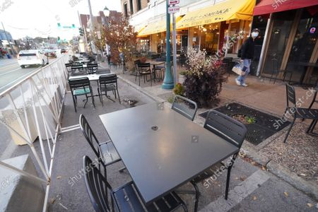 A pedestrian walks past empty tables, wearing masks in the 45 degree temperatures in University City, Missouri on Tuesday, November 17, 2020. Due to the COVID-19 spreading in record numbers, St. Louis County Executive Dr. Sam Page has ordered all restaurants in St. Louis County, closed for indoor seating, however curbside pickup and outdoor seating is still permitted. All people over five years of age must wear a mask when leaving home.