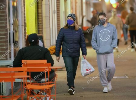 Pedestrians walk past empty tables, wearing masks in the 45 degree temperatures in University City, Missouri on Tuesday, November 17, 2020. Due to the COVID-19 spreading in record numbers, St. Louis County Executive Dr. Sam Page has ordered all restaurants in St. Louis County, closed for indoor seating, however curbside pickup and outdoor seating is still permitted. All people over five years of age must wear a mask when leaving home.