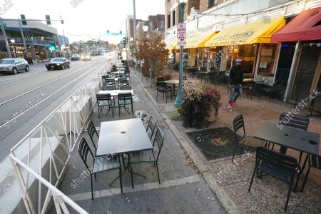 A pedestrian walks past empty tables, in the 45 degree temperatures in University City, Missouri on Tuesday, November 17, 2020. Due to the COVID-19 spreading in record numbers, St. Louis County Executive Dr. Sam Page has ordered all restaurants in St. Louis County, closed for indoor seating, however curbside pickup and outdoor seating is still permitted. All people over five years of age must wear a mask when leaving home.