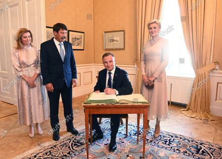 Polish President Andrzej Duda (2ND R) writes in the guest book as his wife Agata Kornhauser-Duda (R), Hungarian President Janos Ader (2ND L) and his wife Anita Herczeg (L) look on during their meeting in the presidential Alexander Palace in Budapest, Hungary, 09 September 2021. President Duda is in Hungary on an official visit.