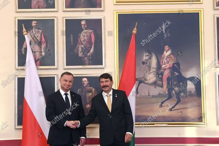 Polish President Andrzej Duda (L) shakes hands with his Hungarian counterpart Janos Ader (R) after receiving the Grand Cross of the Hungarian Order of Merit for his contribution to strenghtening the cooperation between Hungary and Poland during a ceremony held in the Buda Castle in Budapest, Hungary, 09 September 2021.